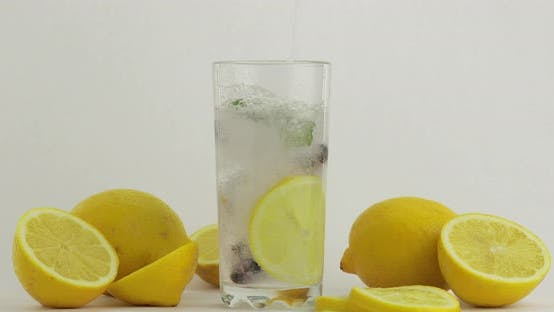 Thumbnail for Pour a Cold Soda Drink. Lemon and Ice in a Drink Glass. Refreshing Cocktail
