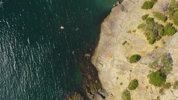 Flying Above Wild Sea  Beach With People. High Angle Aerial View