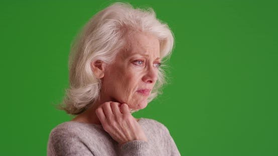 Thumbnail for Depressed older woman resting her hand against her neck on greenscreen