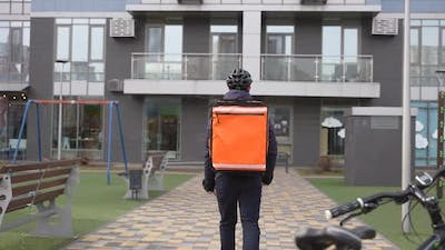 Courier with Thermal Backpack Walking to Building