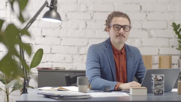 Thumbnail for Caucasian Hipster Entrepreneur Posing at his Desk in Loft Office