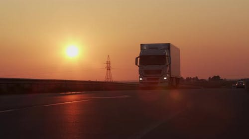 Highway With Moving Trucks At Sunset