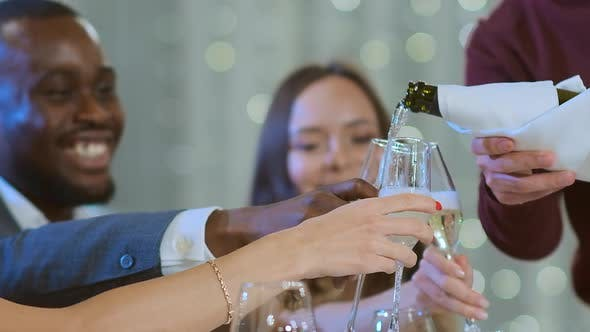 Thumbnail for Slow Motion a Man Pours Champagne To Friends. The Multiethnic Company Celebrates the New Year