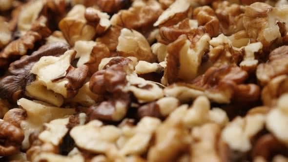 Lot of Juglans regia fruit ingredient pieces 4K 2160p 30fps UltraHD tilting footage - Pile of walnut