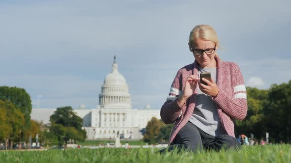 Thumbnail for A Young Woman in Glasses Sits on the Lawn, Enjoys a Smartphone. Against the Backdrop of the Capitol