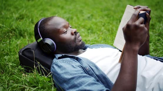 Thumbnail for African-American Man Lying on Lawn with Book