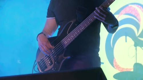 Bass Guitarist at a Rock Concert Plays Guitar on Open Stage. Slow Motion