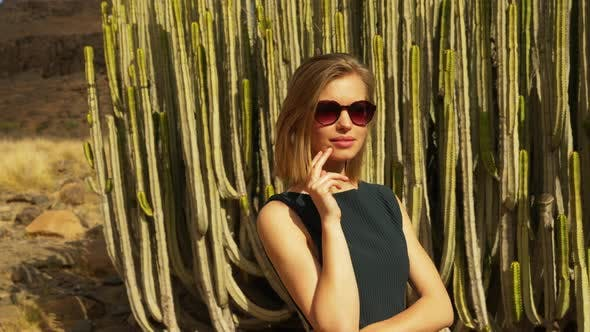 Thumbnail for Model with an Sunglasses Elegantly Posing in Front of Cacti