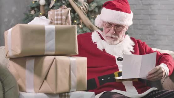 Thumbnail for Portrait of Concentrated Old Santa Claus Reading Letter. Mature Man with White Beard in Eyeglasses