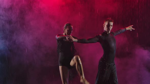 Thumbnail for Young Couple Cheerfully Dancing Jive on a Smoky Background with Crimson Backlight. Slow Motion