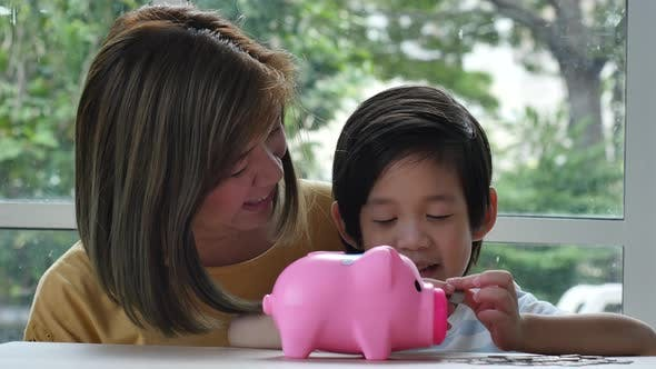 Cute Asian Child And Mother Putting A Coin In To A Piggy Bank