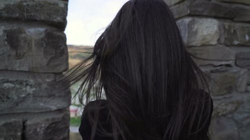 Brunette Girl Watching Trough Medieval Stronghold Wall and Taking Pictures with Smartphone