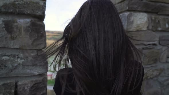 Thumbnail for Brunette Girl Watching Trough Medieval Stronghold Wall and Taking Pictures with Smartphone