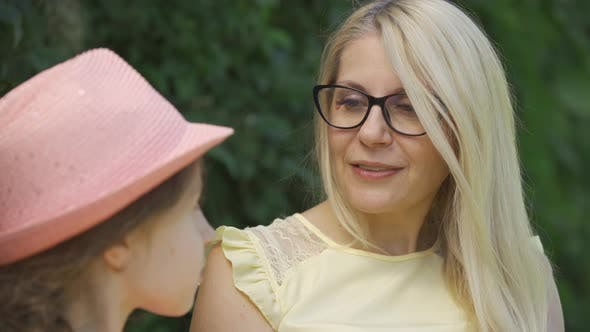 Thumbnail for Portrait Mature Blond Mother in Glasses and Her Little Daughter Talking While Sitting on the Bench