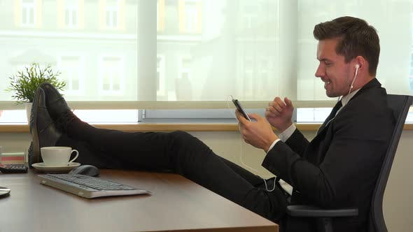 Thumbnail for Worker sits in front of a computer with legs on the desk and listens to music on a smartphone