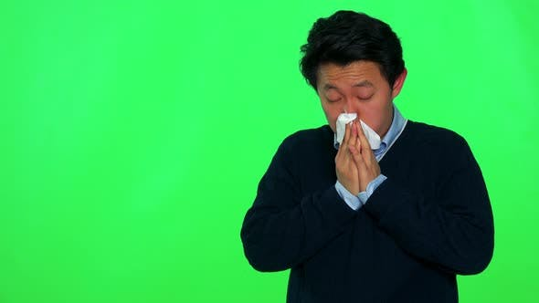 Thumbnail for A Young Asian Is Sick and Blows His Nose Into a Paper Tissue - Green Screen Studio