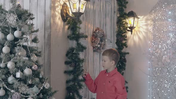 Thumbnail for Blond Boy Child in Red Shirt Adjusts Pine Decor with Cones