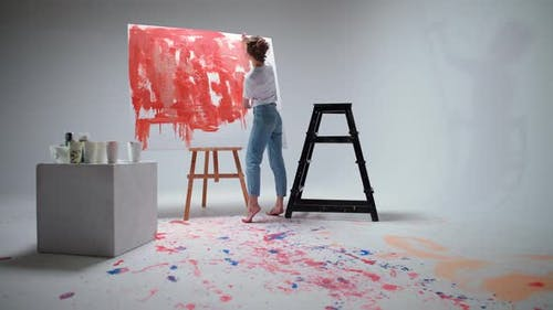Back View Female Artist Draws with a Brush on a Large Canvas in a White Room a Talented Artist Draws