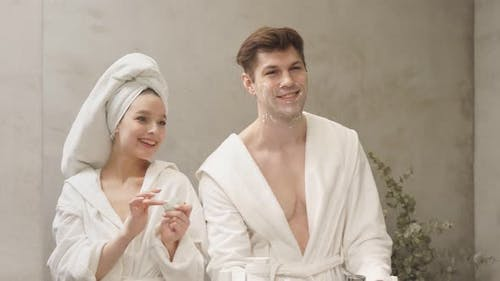 Attractive Female in Bathrobe and Towel Use Moisturizing Cream While Boyfriend Shaving Stubble