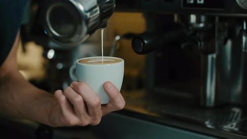 Barista making latte art in  specialty coffee shop.