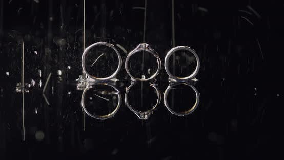 Thumbnail for Wedding and Engagement Rings Lying on Dark Water Surface Shining with Light