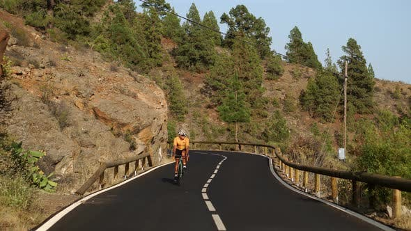 Thumbnail for A Man in a Yellow T-shirt on a Sports Road Bike Rides on the Road Located High in the Mountains