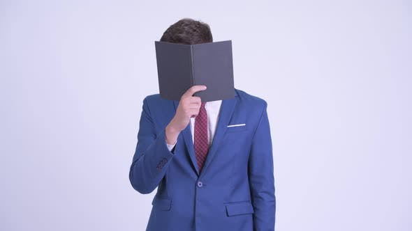 Thumbnail for Young Businessman Covering Face with Book