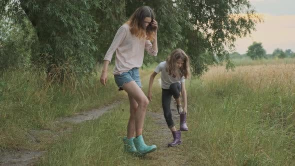 Thumbnail for Two Happy Girls Sisters Walking After Rain in Dirty Clothes Fun Pouring Water From Their Boots