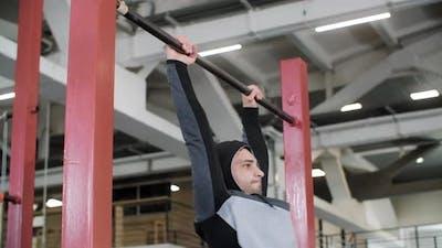 Athletic Man in Hood Exercising on Crossbar