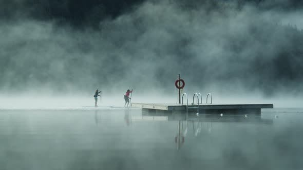 Thumbnail for A Couple of Paddle Boarders Passing by a Wooden Diving Spot on a Foggy Lake