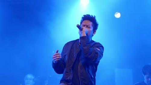 Asiatischer Vocal-Rockstar-Band-Musiker tritt auf der Bühne im Nachtclub mit Rampenlicht auf