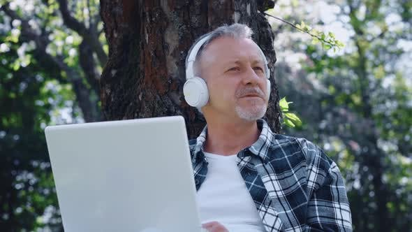 An Elderly Grayhaired Man with a Beard in Headphones Enjoys Music and Nature Sitting with a Laptop