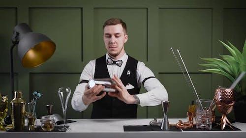 Ein gutaussehender männlicher Barkeeper führt Tricks mit einem Shaker durch. Ein Profi wirft und fängt einen Shaker.