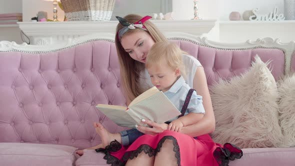 Thumbnail for Portrait of Confident Young Mother Sitting with Cute Little Son on Pink Couch and Reading Book