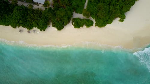 Daytime drone tourism shot of a paradise sunny white sand beach and aqua blue ocean background in be