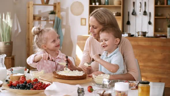 Thumbnail for Young Caucasian Mom and Kids Making Layered Berry Cake