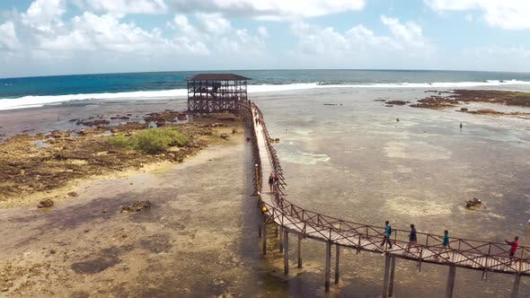 Cover Image for Vacation on Tropical Island. Young Couple Standing on a Wooden Bridge on Cloud 9 Surfing Spot