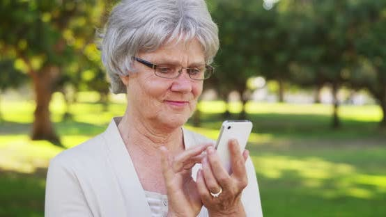 Thumbnail for Senior woman texting on smartphone at the park