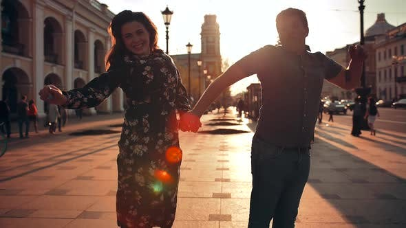 Thumbnail for Playful Happy Young Couple Is Jumping Down the Street and Laughing.
