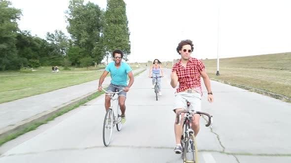Three young adults having fun cycling
