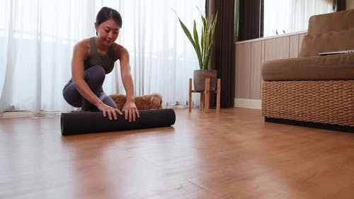 young Asia woman unrolling roll black yoga mat for playing yoga with her dog at home