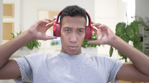 Cover Image for African Man Removing Red Headphones after Listening Music