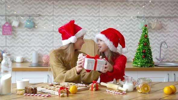 Little Girls with Gift on Christmas in Decorated Living Room