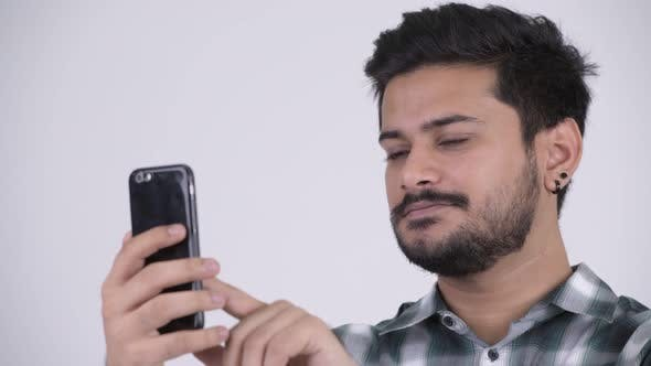 Thumbnail for Portrait of Young Happy Bearded Indian Man Using Phone