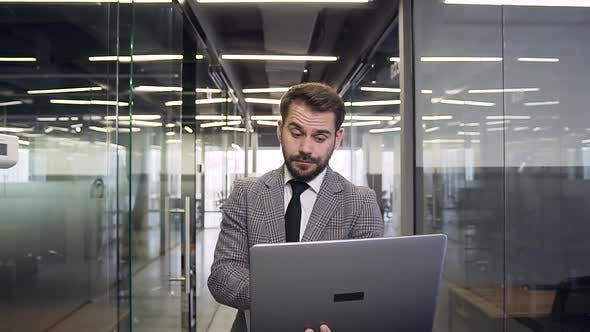 Businessman with Computer Walking through the Modern Company Hall