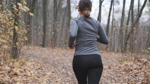 Woman losing weight through everyday running workouts in the park before work. Running concept