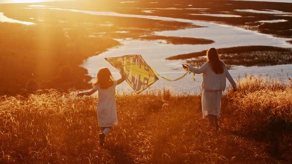 Young Woman with Her Daughter Walking Downhill with the Kite at Sunset