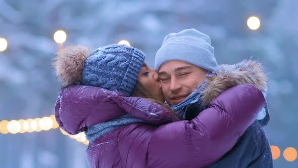 Guy and Girl in Warm Jackets Hug Standing on Skating Rink