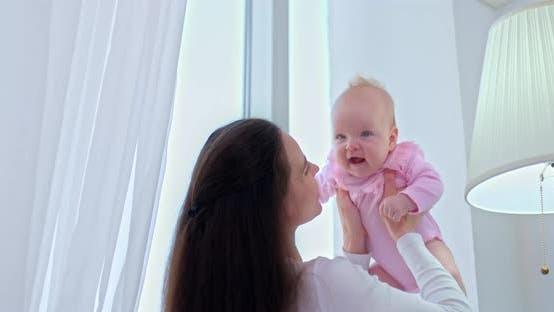 Portrait, fürsorgliche und schöne Mutter hält das Baby in den Armen und wirft es hoch, das Baby lächelt