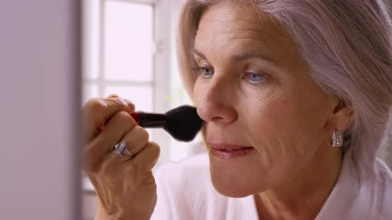 Beautiful mid aged white woman applying makeup